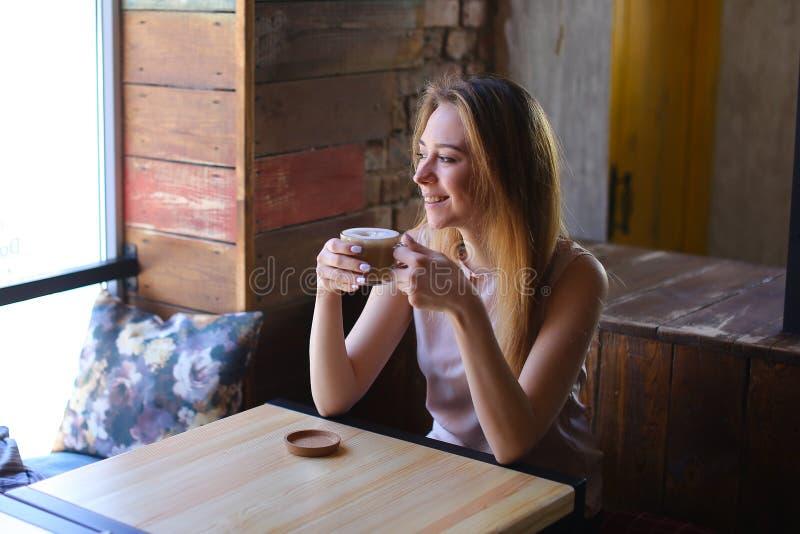 Jovem mulher com o copo do cappuccino à disposição que senta-se perto da janela no café acolhedor fotografia de stock