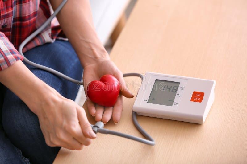 Jovem mulher com o coração pequeno que mede sua pressão sanguínea em casa imagem de stock