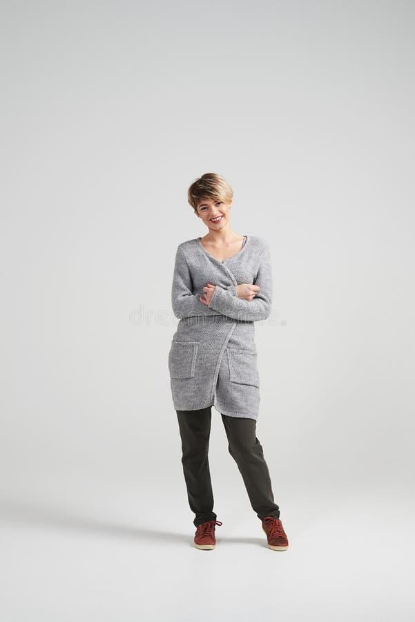 Jovem mulher com o corte de cabelo curto à moda que levanta na câmera foto de stock