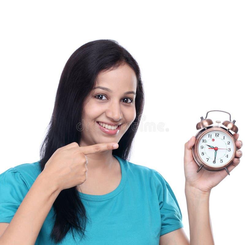 Jovem mulher com o despertador da antiguidade do estilo antigo foto de stock