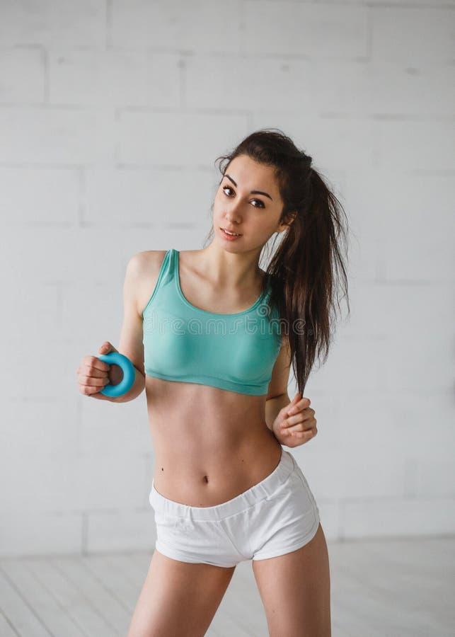 Jovem mulher com o expansor no estúdio do gym imagens de stock