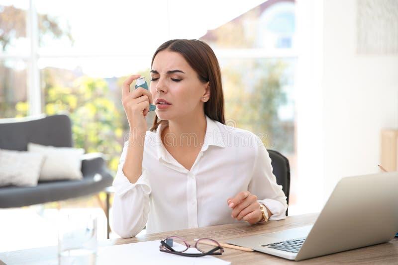 Jovem mulher com o inalador da asma na tabela fotografia de stock royalty free