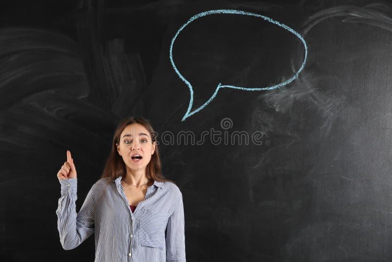 Jovem mulher com o indicador aumentado perto da bolha vazia do discurso tirada no quadro-negro imagens de stock royalty free