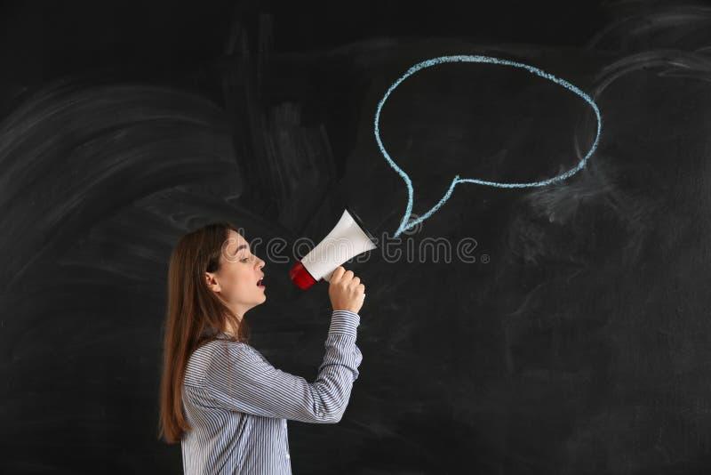 Jovem mulher com o megafone perto da bolha vazia do discurso tirada no quadro-negro fotos de stock