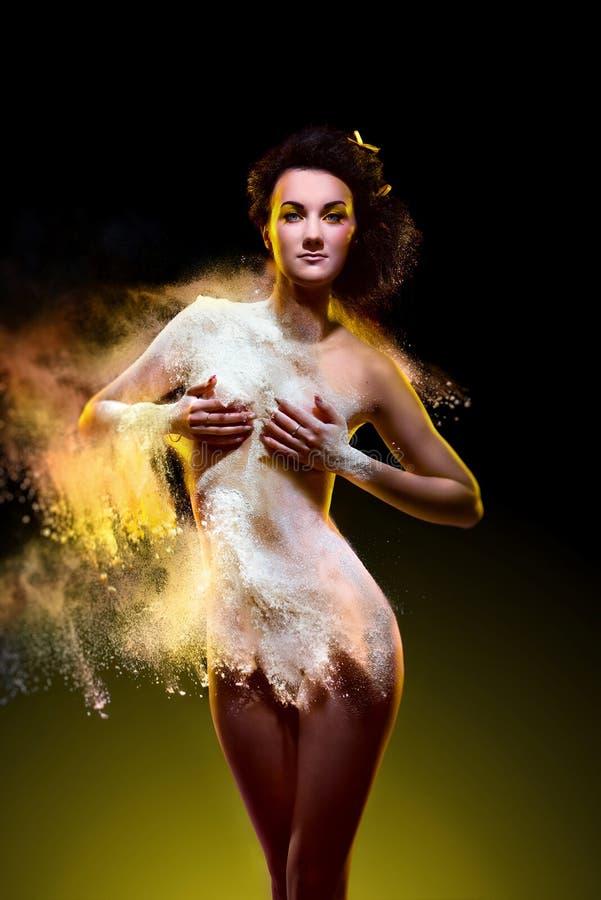 Jovem mulher com o pó colorido que explode em torno dela foto de stock