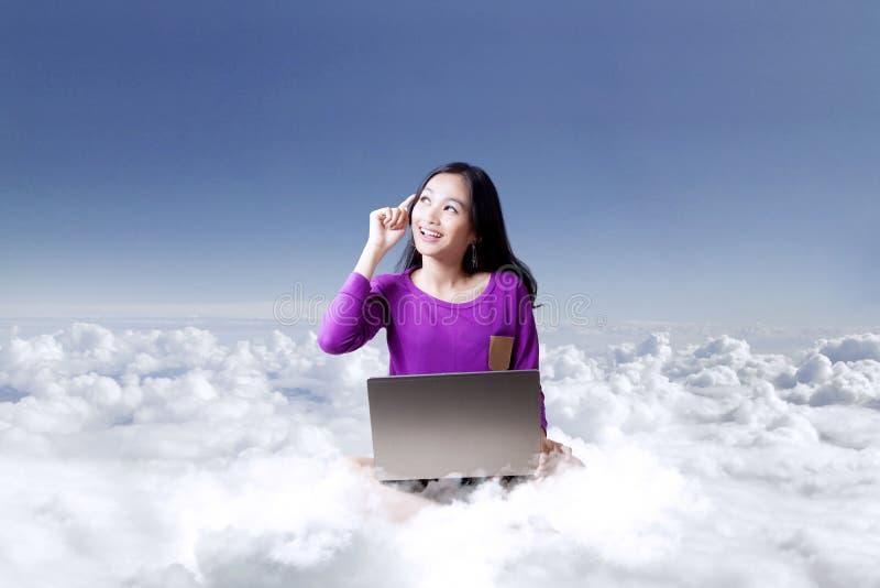 Jovem mulher com o portátil sob o céu azul fotografia de stock