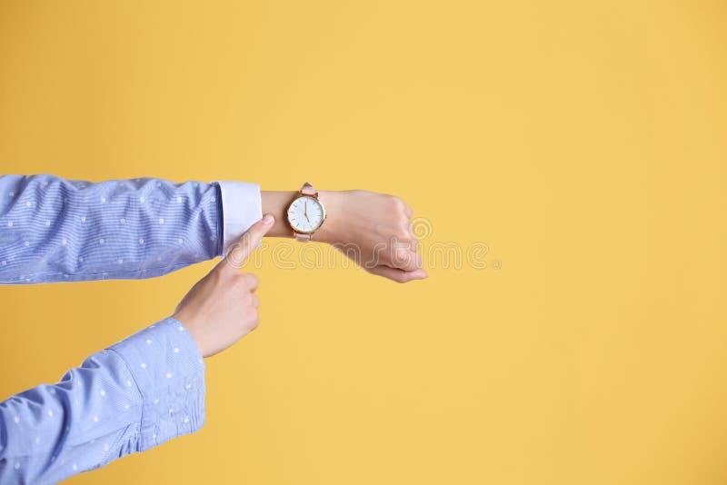 Jovem mulher com o relógio de pulso no fundo da cor fotografia de stock royalty free