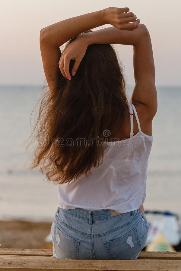 Jovem mulher com o sittin do cabelo encaracolado na praia da manhã fotografia de stock royalty free