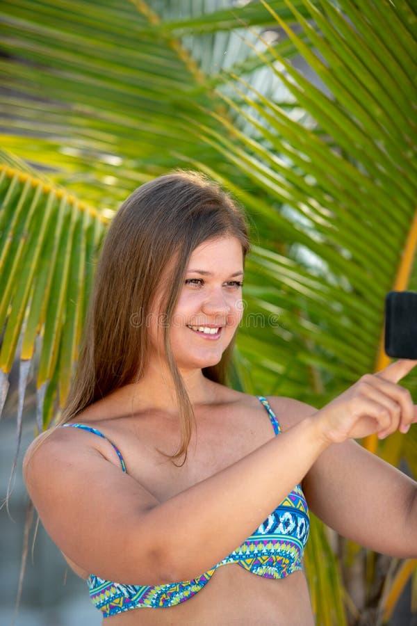 Jovem mulher com o smartphone na frente da palma fotografia de stock royalty free