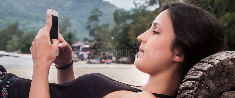 Jovem mulher com o smartphone que relaxa na praia tropical imagem de stock royalty free
