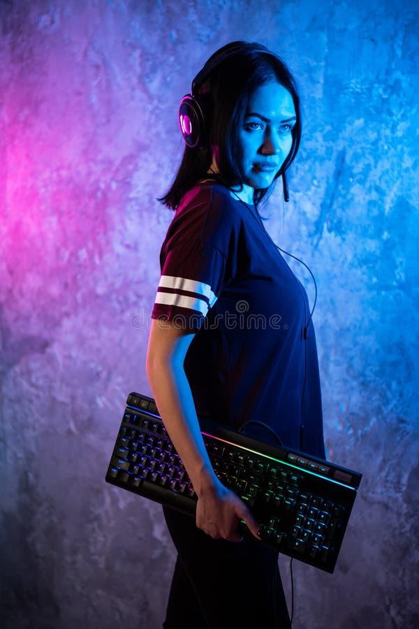 Jovem mulher com o teclado que levanta na frente da parede leve com cores de n?on vermelhas Jogos do Gamer imagens de stock