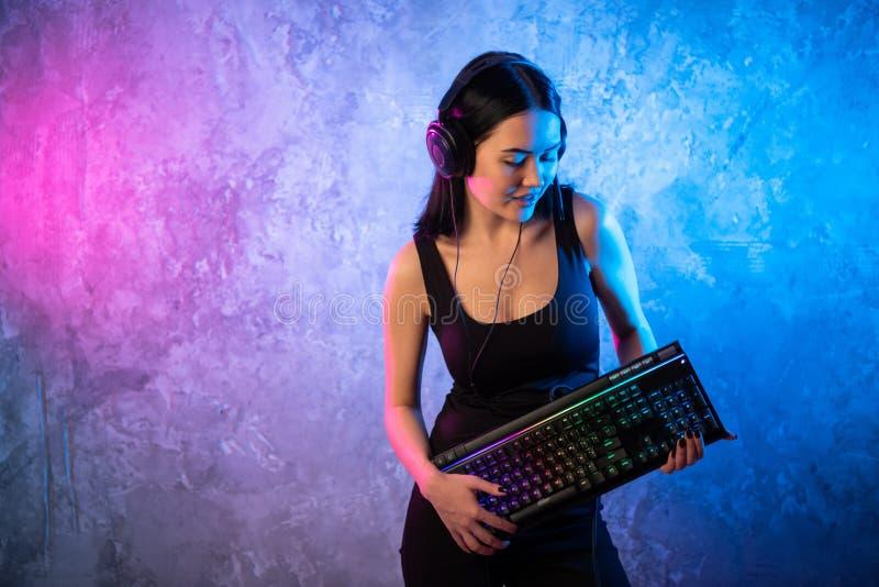 Jovem mulher com o teclado que levanta na frente da parede leve com cores de n?on vermelhas Jogos do Gamer imagens de stock royalty free