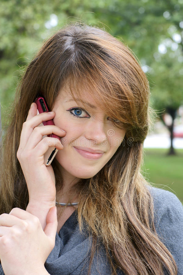 Jovem mulher com o telefone celular que olha a câmera foto de stock royalty free