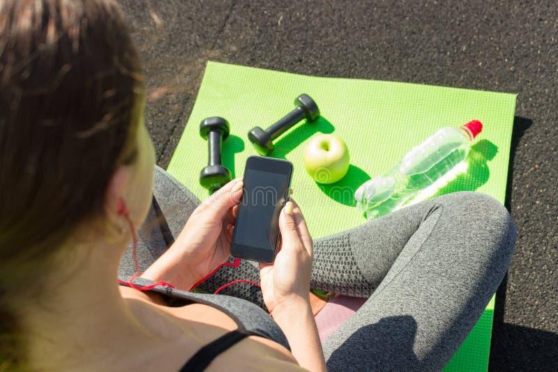 Jovem mulher com o telefone celular que senta-se na esteira perto dos pesos, da maçã e da garrafa da água no assoalho Apronte par foto de stock