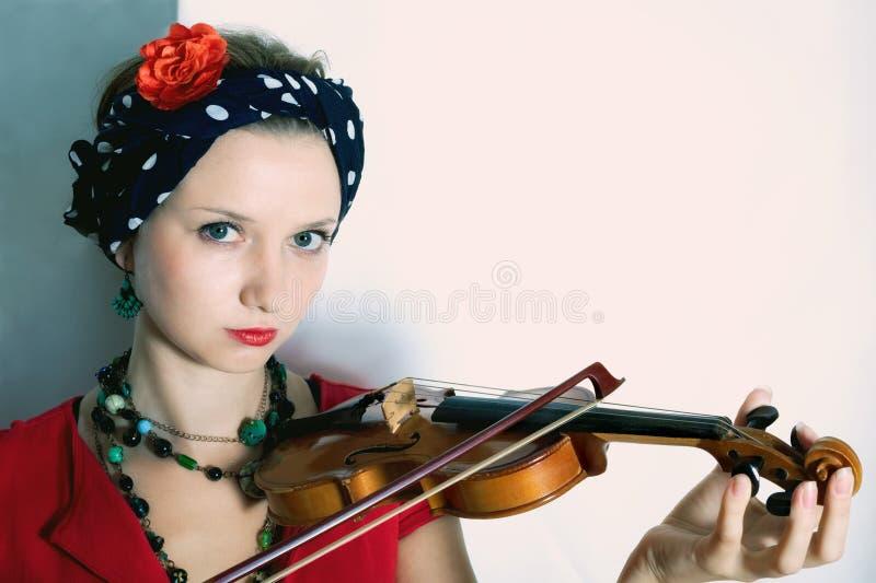 Jovem mulher com o violino no fundo claro foto de stock