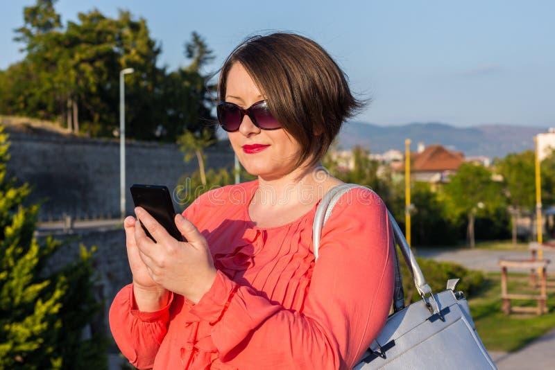 Jovem mulher com os óculos de sol que estão na ponte e que Texting em seu Smartphone fotos de stock royalty free