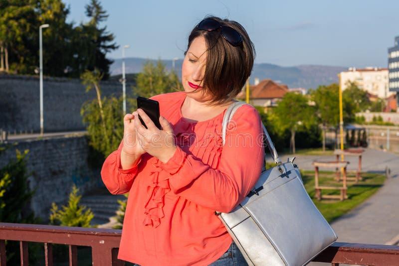 Jovem mulher com os óculos de sol que estão na ponte e que Texting em seu Smartphone fotografia de stock royalty free