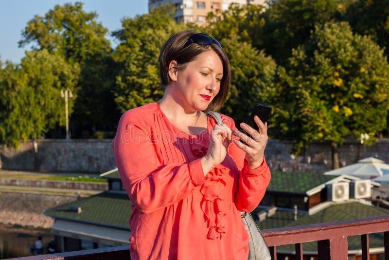 Jovem mulher com os óculos de sol que estão na ponte e que Texting em seu Smartphone imagem de stock royalty free