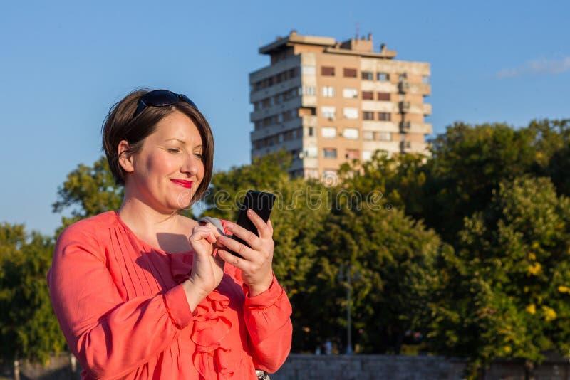 Jovem mulher com os óculos de sol que estão na ponte e que Texting em seu Smartphone fotos de stock