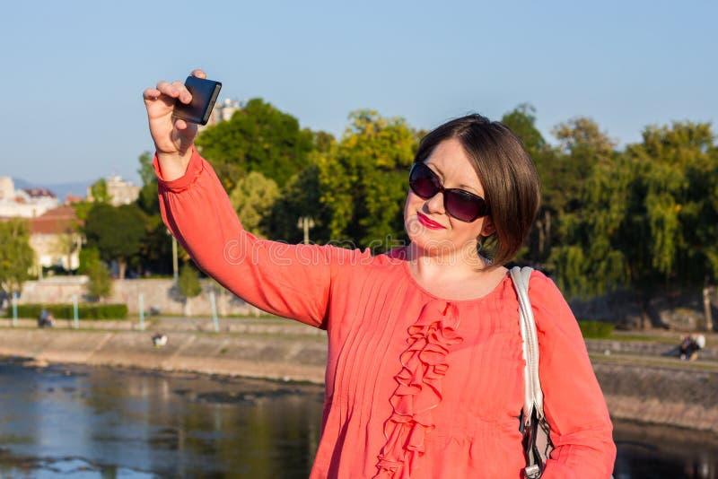 Jovem mulher com os óculos de sol que estão na ponte e que tomam Selfie fotografia de stock