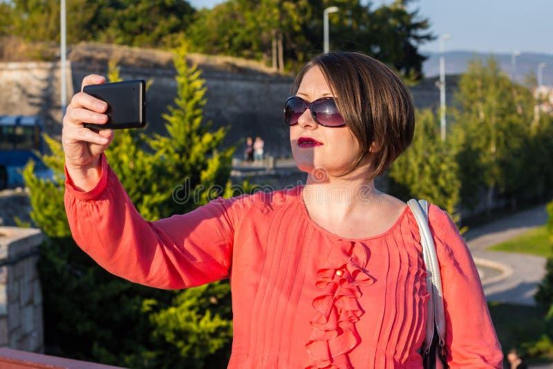 Jovem mulher com os óculos de sol que estão na ponte e que tomam Selfie imagem de stock