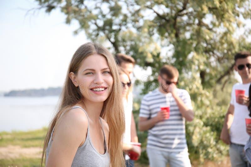 Jovem mulher com os amigos no partido no dia ensolarado fora imagens de stock