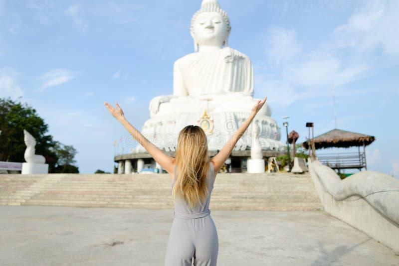 Jovem mulher com os braços estendido que estão perto da estátua concreta da Buda em Phuket imagens de stock royalty free