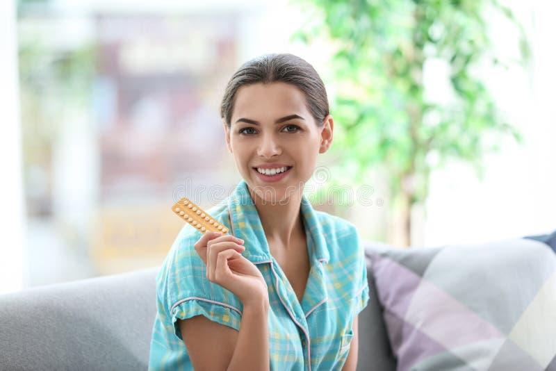 Jovem mulher com os comprimidos de controlo da natalidade em casa foto de stock royalty free
