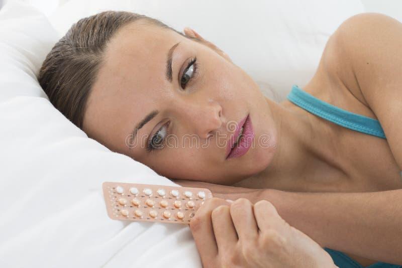 Jovem mulher com os comprimidos de controlo da natalidade na cama fotografia de stock royalty free