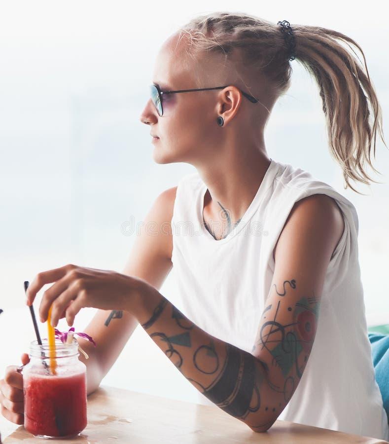 Jovem mulher com os dreadlocks que sentam-se no batido bebendo do café fotos de stock royalty free