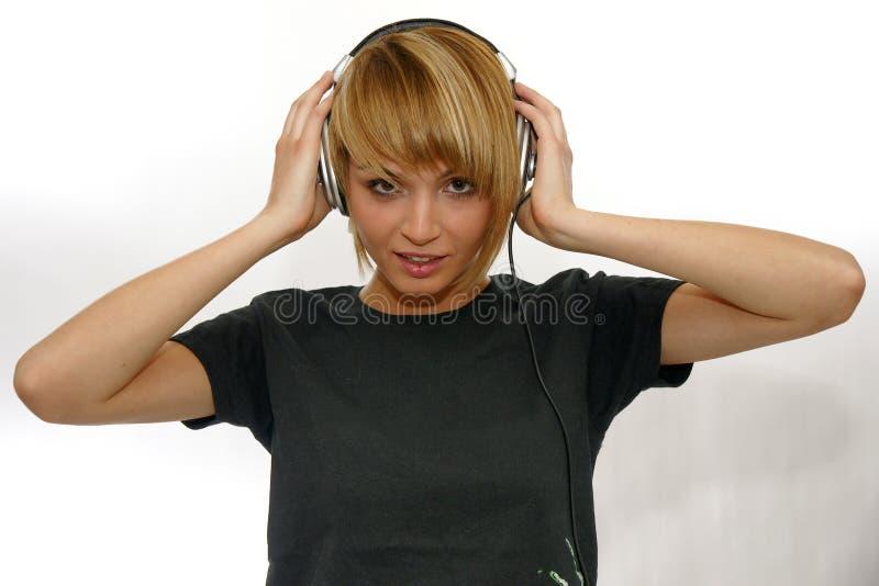Jovem mulher com os fones de ouvido, escutando a música imagem de stock