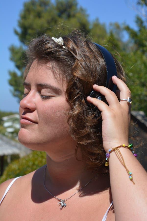 Jovem mulher com os fones de ouvido sem fio, escutando a m?sica no jardim foto de stock royalty free