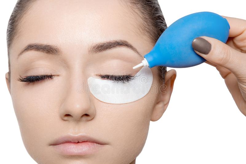 Jovem mulher com os olhos fechados aplicando a colagem para chicotes do olho Vista horizontal imagens de stock