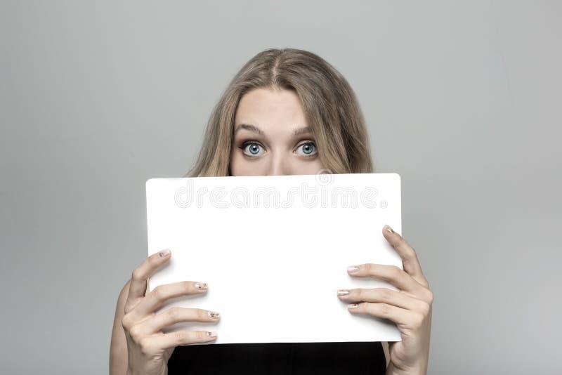 Jovem mulher com os olhos surpreendidos que espreitam para fora do cartaz de trás do papel do quadro de avisos foto de stock