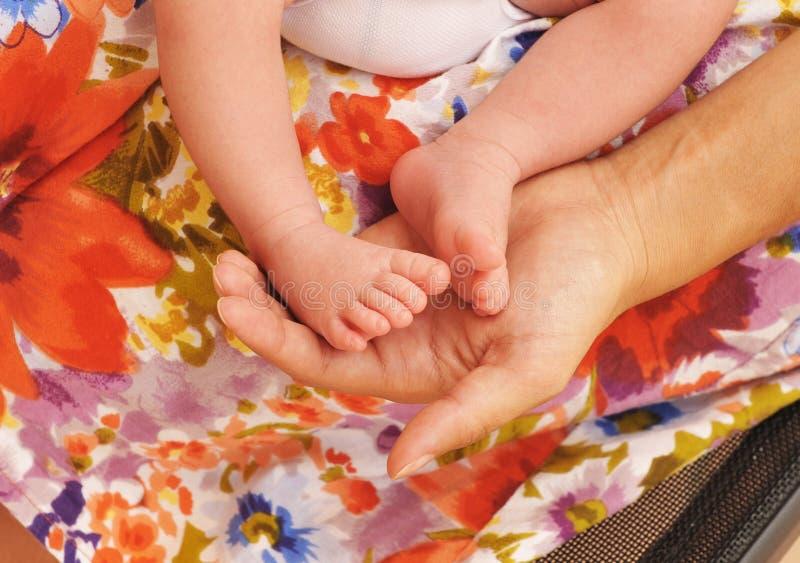 Jovem mulher com os pés pequenos de seu bebê nas mãos fotografia de stock