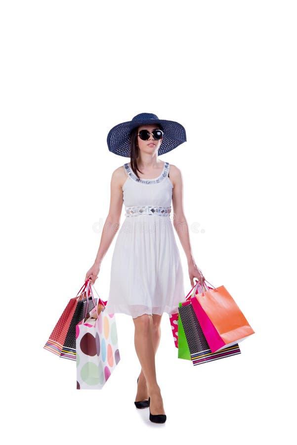 A jovem mulher com os sacos de compras do Natal no branco imagem de stock