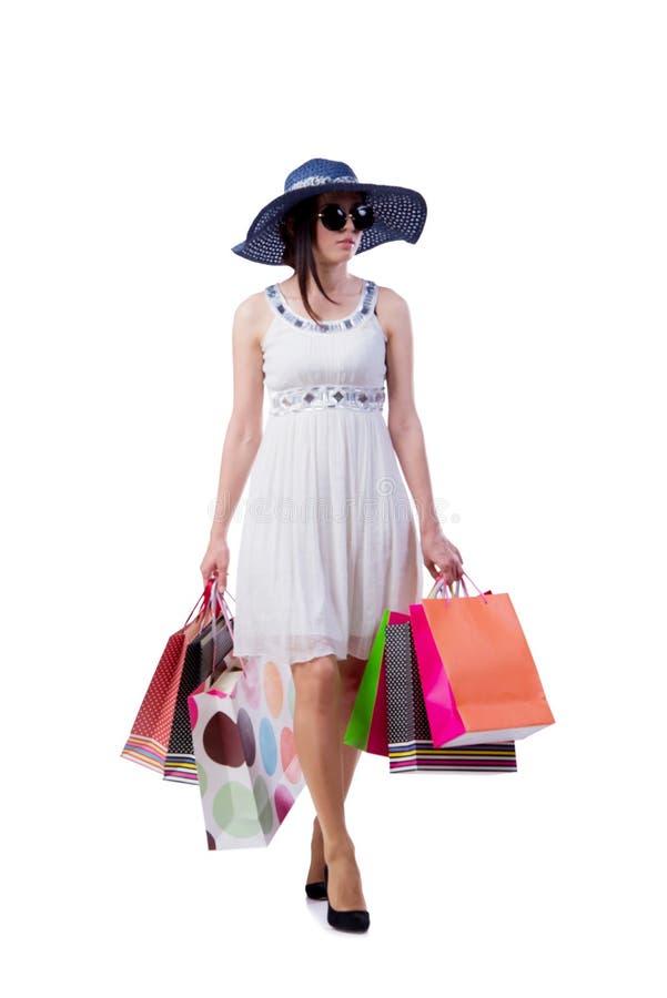A jovem mulher com os sacos de compras do Natal no branco fotografia de stock royalty free