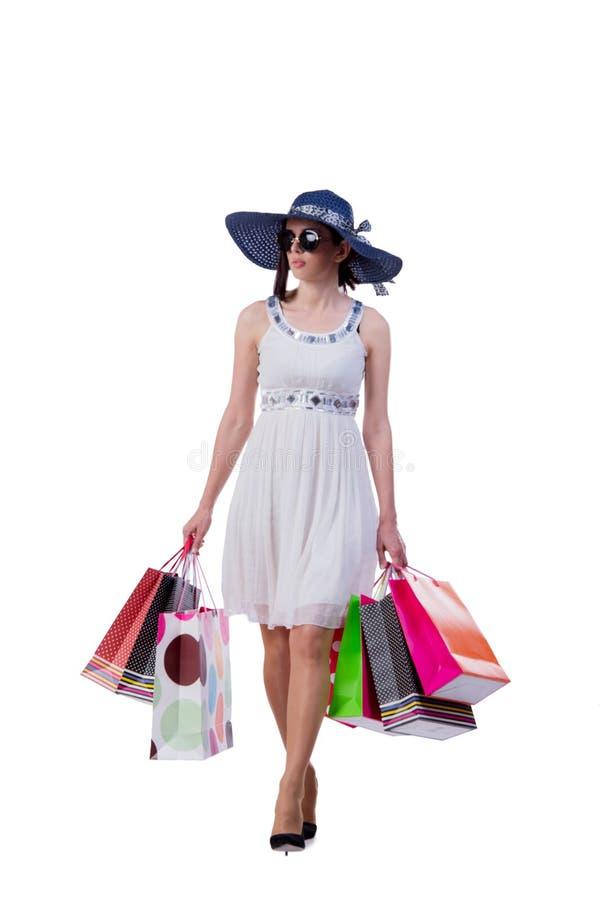 A jovem mulher com os sacos de compras do Natal no branco foto de stock