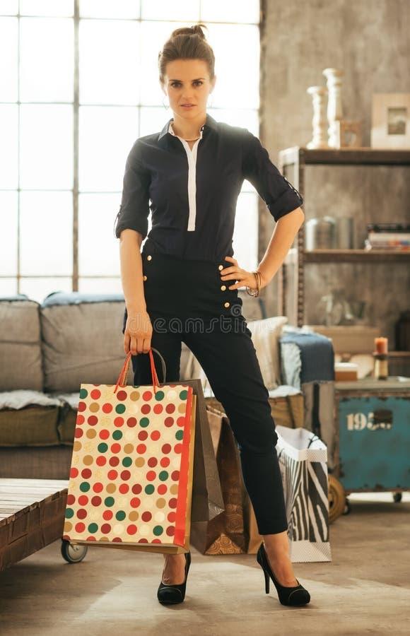 Jovem mulher com os sacos de compras no apartamento do sótão foto de stock