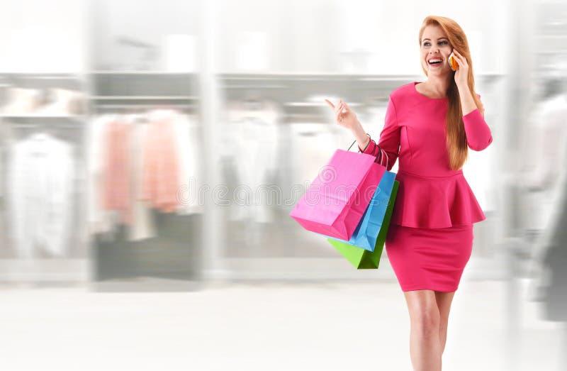 Jovem mulher com os sacos de compras no shopping foto de stock