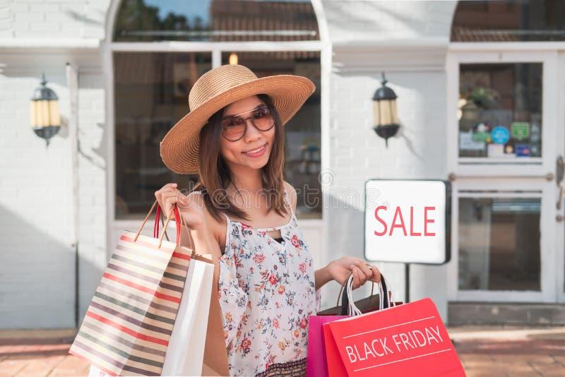 Jovem mulher com os sacos de compras no shopping em sexta-feira preta, conceito do estilo de vida da mulher foto de stock