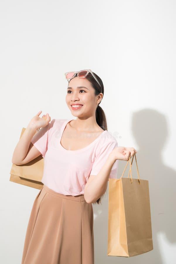 Jovem mulher com os sacos de compras sobre o fundo branco imagens de stock