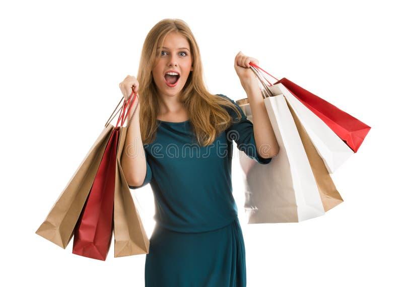 Jovem mulher com os sacos de compras sobre o fundo branco que grita foto de stock