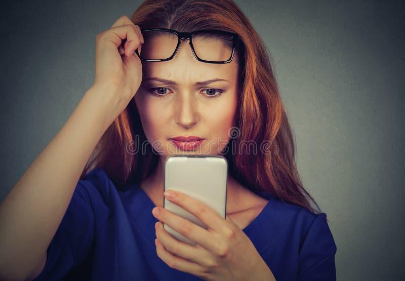 A jovem mulher com os vidros que têm o problema que vê o telefone celular tem problemas da visão fotos de stock royalty free