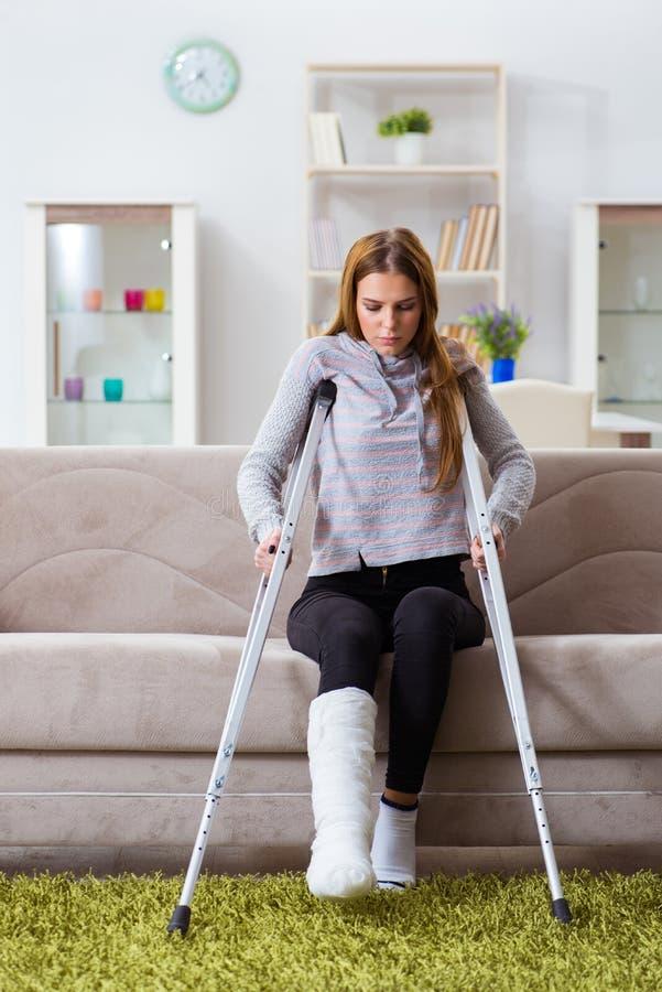 A jovem mulher com pé quebrado em casa imagem de stock