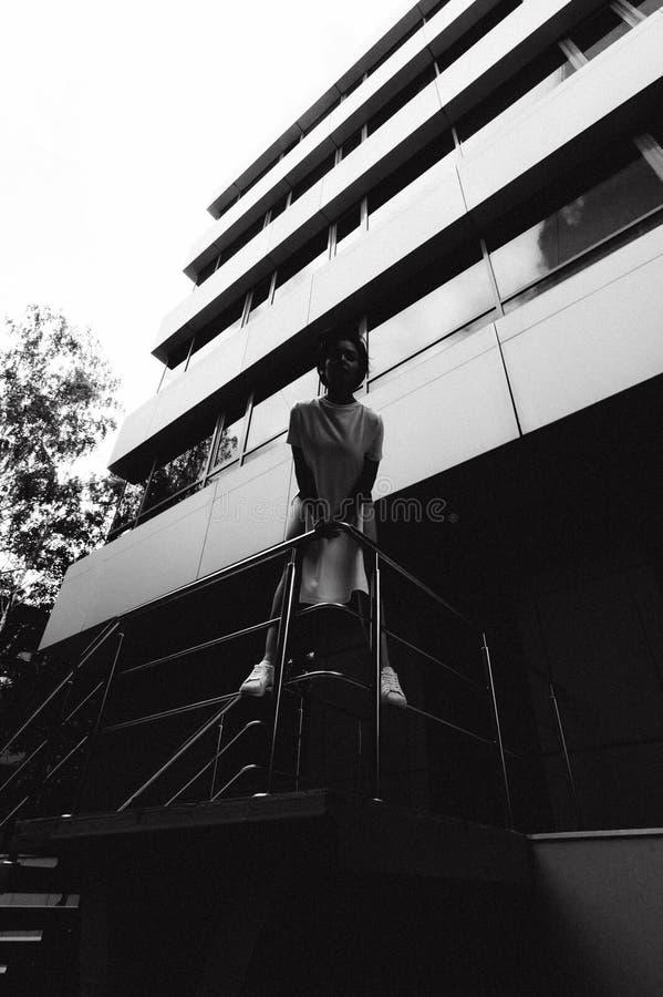 A jovem mulher com pés desencapados vestiu-se nas sapatilhas brancas e em um t-shirt longo, contra o contexto das arquiteturas da foto de stock royalty free