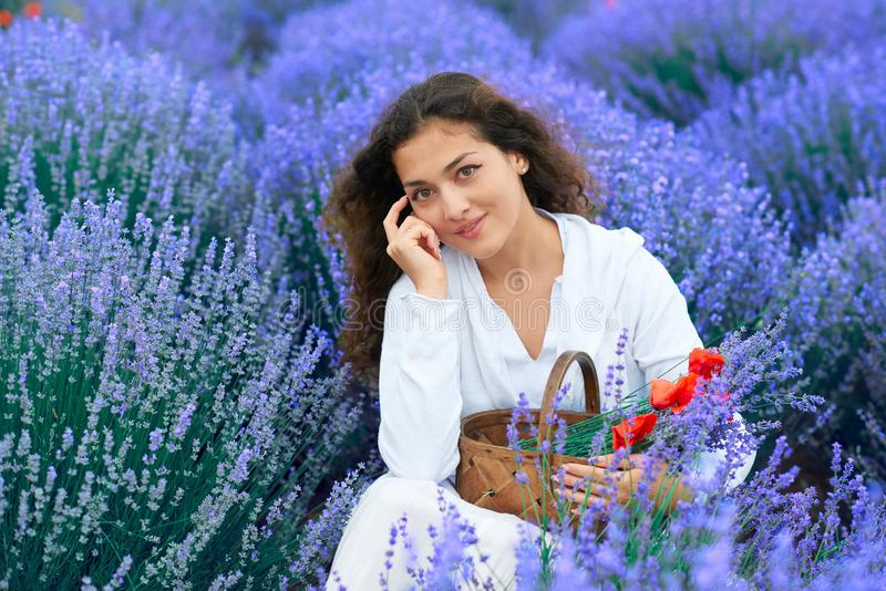 A jovem mulher com papoila est? no campo de flor da alfazema, paisagem bonita do ver?o fotos de stock