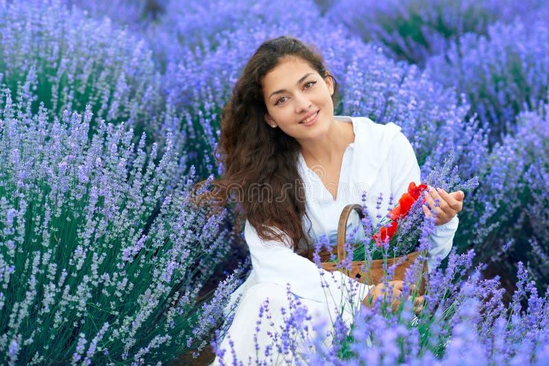 A jovem mulher com papoila est? no campo de flor da alfazema, paisagem bonita do ver?o imagem de stock