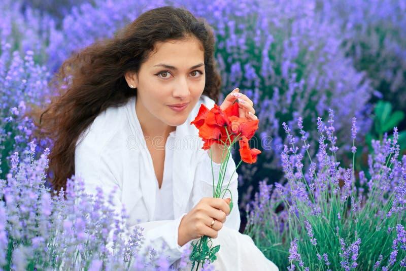 A jovem mulher com papoila est? no campo de flor da alfazema, paisagem bonita do ver?o imagens de stock