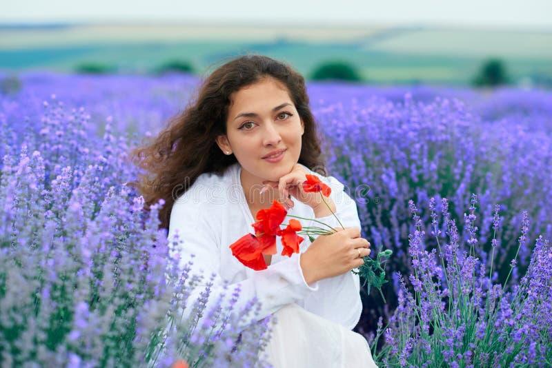 A jovem mulher com papoila est? no campo de flor da alfazema, paisagem bonita do ver?o foto de stock